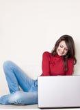 Ragazza piacevole che si siede con il computer portatile e sorridere Immagine Stock