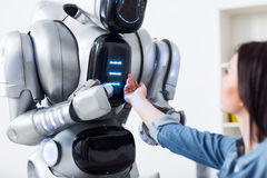 Ragazza piacevole che tocca il robot fotografia stock libera da diritti