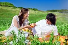 Ragazza piacevole con frutta ed il ragazzo con il sorriso Fotografie Stock Libere da Diritti