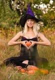 Ragazza piacevole in costume della strega che si siede nella posa del loto Immagini Stock