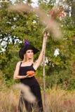 Ragazza piacevole in costume della strega con il manico di scopa Fotografie Stock
