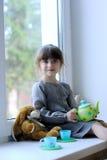 Ragazza piacevole del bambino con l'insieme ed il coniglietto di tè del giocattolo Fotografie Stock Libere da Diritti
