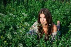 Ragazza piacevole fra erba verde ed i fiori Immagini Stock Libere da Diritti