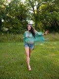 Ragazza a piedi nudi che funziona attraverso l'erba Fotografie Stock Libere da Diritti