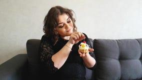 Ragazza piena del cutel di Beautifu con le torte sul sofà archivi video