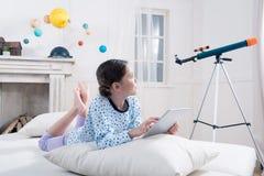 Ragazza in pigiami che si trovano sul letto con la compressa digitale e che esaminano telescopio immagini stock