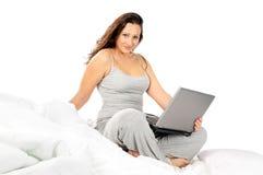 Ragazza in pigiami con il computer portatile Fotografie Stock