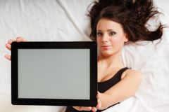 Ragazza pigra sexy che si trova con il touchpad della compressa sul letto Fotografia Stock Libera da Diritti