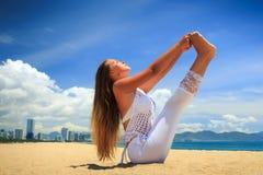 ragazza in pizzo in barca piena di asana di yoga sulla spiaggia Fotografia Stock Libera da Diritti