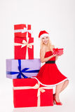 Ragazza positiva nella seduta rossa del vestito e del cappello dal Babbo Natale Fotografia Stock Libera da Diritti