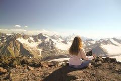 Ragazza premurosa che si siede sopra una montagna durante il campeggio Fotografie Stock