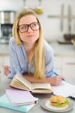 Ragazza premurosa dell'adolescente che studia nella cucina Fotografia Stock