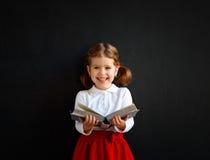 Ragazza prescolare della scolara felice con il libro vicino alla lavagna della scuola Fotografie Stock