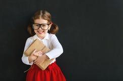 Ragazza prescolare della scolara felice con il libro vicino alla lavagna della scuola Fotografia Stock