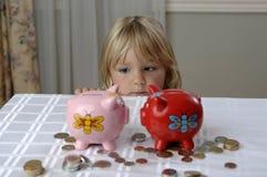Ragazza prescolare e banche piggy Fotografia Stock Libera da Diritti