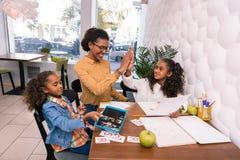 Ragazza prescolare felice che dà su cinque al suo insegnante della scuola materna immagine stock libera da diritti