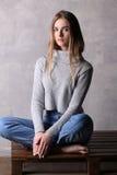 Ragazza in pullover che si siede su una piattaforma Fondo grigio Fotografie Stock Libere da Diritti