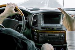 Ragazza, punti un dito all'uomo, autista, dal momento che quando sta conducendo un'automobile, nell'inverno, nella m. innevata fotografia stock