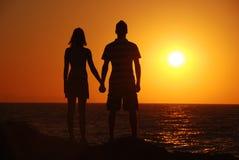 Ragazza, ragazzo, mare e tramonto Fotografie Stock