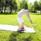 Ragazza reale bionda che fa yoga in parco verde, testa relativa alla ginnastica sopra la h Fotografia Stock