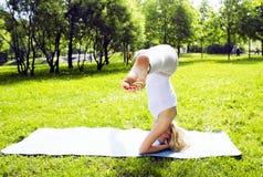 Ragazza reale bionda che fa yoga in parco verde, testa relativa alla ginnastica sopra le colline fuori, concetto della gente di s Fotografia Stock