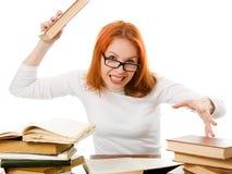 Ragazza red-haired arrabbiata in vetri con i libri Immagine Stock