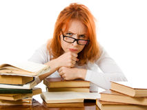 Ragazza red-haired faticosa in vetri con i libri Immagine Stock