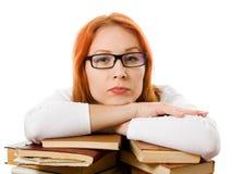 Ragazza red-haired seria in vetri con i libri. Fotografie Stock