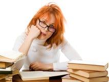 Ragazza red-haired stancare in vetri con i libri. Immagini Stock