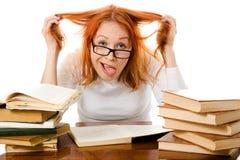Ragazza Red-haired in vetri con i libri Immagini Stock Libere da Diritti