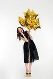 Ragazza riccia adorabile allegra in modo divertente che tiene i palloni dorati Fotografia Stock