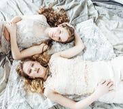 Ragazza riccia bionda dell'acconciatura della sorella gemellata graziosa due in hous di lusso Immagine Stock