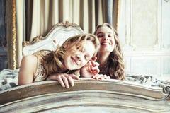Ragazza riccia bionda dell'acconciatura della sorella gemellata graziosa due in hous di lusso fotografie stock