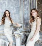 Ragazza riccia bionda dell'acconciatura della sorella gemellata graziosa due nell'interno di lusso della casa insieme, concetto r Fotografie Stock Libere da Diritti