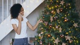 Ragazza riccia della corsa mista che decora l'albero di Natale a casa e che chiacchiera facendo uso dello smartphone Fotografia Stock Libera da Diritti