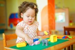 Ragazza riccia kazaka che gioca nel centro di sviluppo dei bambini Immagine Stock