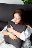 Ragazza rilassata che abbraccia un cuscino Fotografie Stock Libere da Diritti