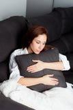Ragazza rilassata che abbraccia un cuscino Fotografia Stock