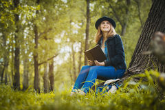 Ragazza rilassata che legge un libro sotto un albero Immagini Stock