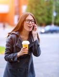 Ragazza in rivestimento che parla emozionalmente sul telefono, le maledizioni gridanti, tenendo un caffè o un tè, giovani all'ape Immagini Stock Libere da Diritti