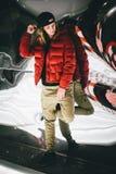 Ragazza in rivestimento rosso che indossa cappuccio alla moda che si appoggia vetro falso immagini stock libere da diritti