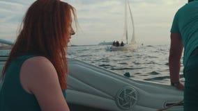 Ragazza rossa dei capelli che si siede in imbarcazione a motore con l'uomo Sera di estate intrattenimento archivi video