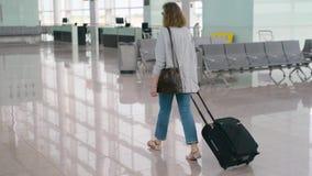 Ragazza rossa della donna dei capelli dello zenzero che cammina con la borsa della valigia dei bagagli di rotolamento archivi video