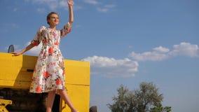Ragazza rurale nell'ondeggiamento del vestito della mano che sta sul cofano del trattore alla natura su fondo del cielo archivi video