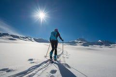 Ragazza in salita con alpinismo delle pelli e dello sci della guarnizione Fotografia Stock Libera da Diritti