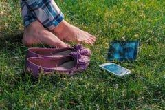 Ragazza scalza che si rilassa a gambe accavallate sull'erba con il compressa-pc e lo smartphone immagini stock libere da diritti