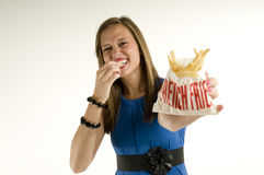 Ragazza scarna che mangia le patate fritte Fotografia Stock