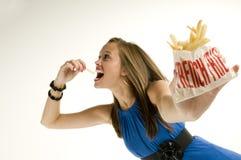 Ragazza scarna che mangia le patate fritte Fotografie Stock