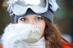 Ragazza in sciatore in vestiti e caffè luminosi Fotografia Stock