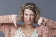 Ragazza scontrosa che esprime repulsione, disaccordo ed avversione con i pollici giù Fotografia Stock